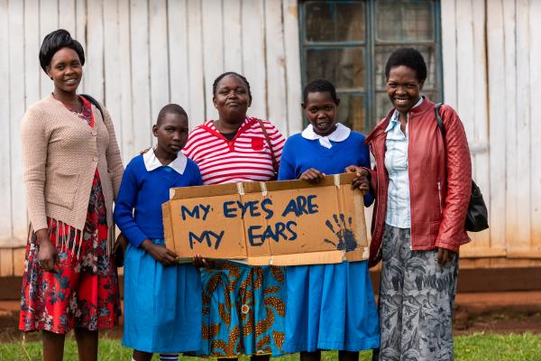 four people stood outside a building holding a sign that says 'my ears are my ears'