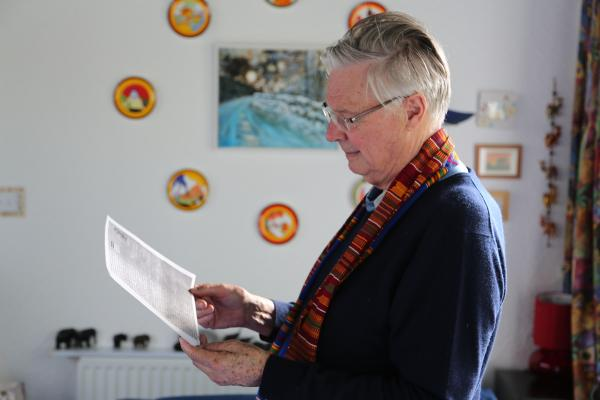 Volunteer Chris Tipple looks at a letter he wrote to VSO's founder, Alec Dickson