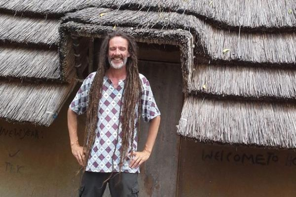 man stood outside a hut in south sudan