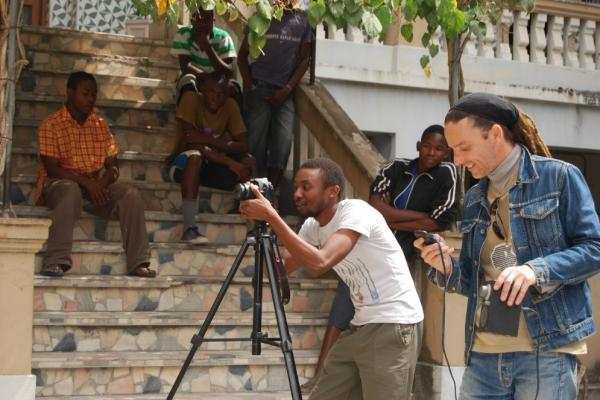 Two men stood outside with a camera, filming